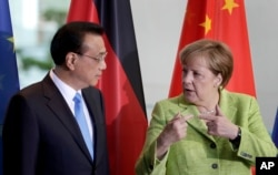 FILE - German Chancellor Angela Merkel and Chinese Premier Li Keqiang talk during a contract signing ceremony as part of a meeting at the chancellery in Berlin, June 1, 2017.