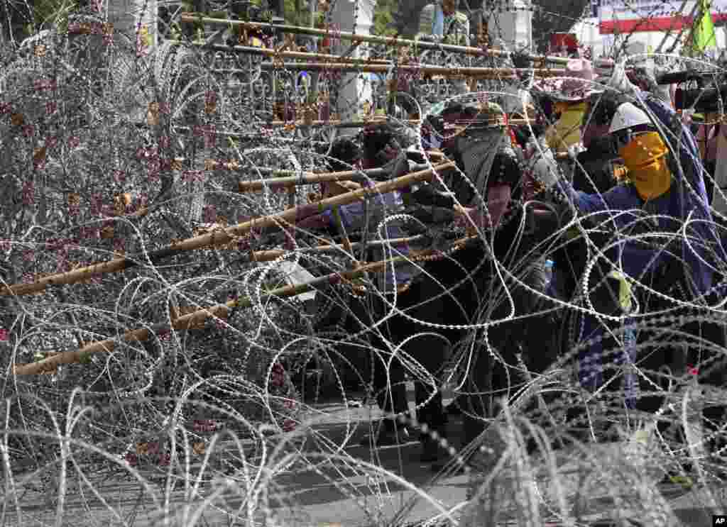 Anti-government protesters use a ladder as they try to remove barbed wire placed inside a gate at Government House in Bangkok, Dec. 12, 2013.