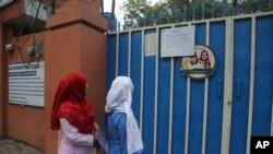 لاہور میں کچھ طالبات اسکول بند ہونے کا نوٹی فکیشن پڑھ رہی ہیں۔