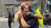 Manifestantes se abrazan en una protesta en Washington, Minnesota, no llevan máscaras y no guardan una distancia social apropiada de protección contra el coronavirus. [Foto: Ronec Suarc, VOA]