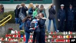 Düşen uçaktaki ölen Alman lise öğrencilerinin arkadaşları okul binası önünde kucaklaşırken
