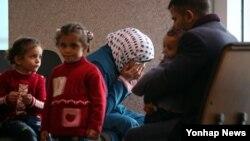 18일 시리아에서 한국에 도착한 난민이라고 밝힌 여성이 남편으로 추정되는 남성, 아이 셋과 함께 영종도 인천국제공항 내 입국심사장 인근에 앉아 대기하던 중 눈물을 흘리고 있다.