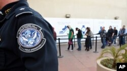 FILE - In this Dec. 10, 2015, file photo, pedestrians crossing from Mexico into the United States at the Otay Mesa Port of Entry wait in line in San Diego. The Trump administration is proposing rules that could deny green cards to immigrants if they…