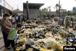 Orang-orang berdiri di samping bunga yang ditempatkan di pintu masuk stasiun kereta bawah tanah Metro Line 5 untuk mengenang korban banjir yang dipicu oleh hujan deras di Zhengzhou, provinsi Henan, China, 27 Juli 2021. (China Daily via REUTERS)