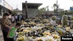 资料照片:在中国河南省郑州市,人们站在摆满鲜花的郑州地铁5号线地铁站入口处,纪念在洪灾中失去生命的乘客。(2021年7月27日)