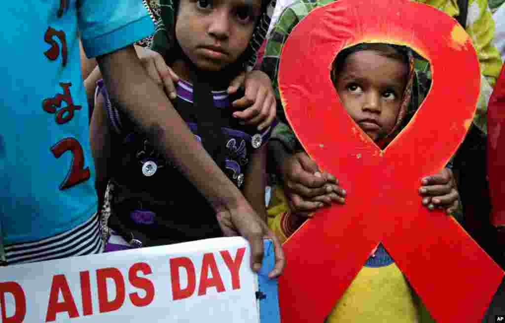 2012年11月30日,在印度加爾各答,孩子們和活動人士一起在世界愛滋病日前夕舉行火炬集會。活動人士要求為性工作者、愛滋病患者及病毒攜帶者提供每月退休金及免費分發物品的設施。