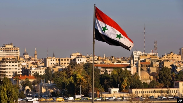FILE - A Syrian national flag waves as vehicles move slowly on a bridge during rush hour, in Damascus, Syria, Feb. 28, 2016.