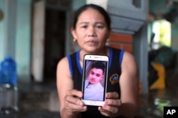 Hoang Thi Ai holds up her phone showing a photo of her son Hoang Van Tiep, who she fears is one of the possible victims in the truck deaths in England, at her home in Nghe An province, Vietnam on Monday, Oct. 28, 2019. (AP Photo/Hau Dinh)
