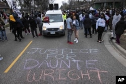 People gather in protest, Sunday, April 11, 2021, in Brooklyn Center, Minn. The family of Daunte Wright, 20, told a crowd that he was shot by police Sunday before getting back into his car and driving away, then crashing the vehicle several blocks away. T