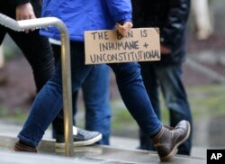"""A person walks away from the federal courthouse in Seattle carrying a sign that reads """"The Ban is Inhumane and Unconstitutional"""" following a hearing in federal court in Seattle, Feb. 3, 2017."""