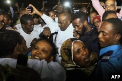 FILE - Family members welcome their loved ones after Sudan released dozens of opposition activists who were arrested last month when authorities cracked down on protests against rising food prices, outside the Kobar prison in north Khartoum on Feb. 18, 20