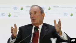 "FILE - Former New York City Mayor Michael Bloomberg, right, gestures as he speaks during a panel discussion on ""Climate Change and Financial Markets""at the COP21, United Nations Climate Change Conference, in Le Bourget north of Paris, Dec. 4, 2015."