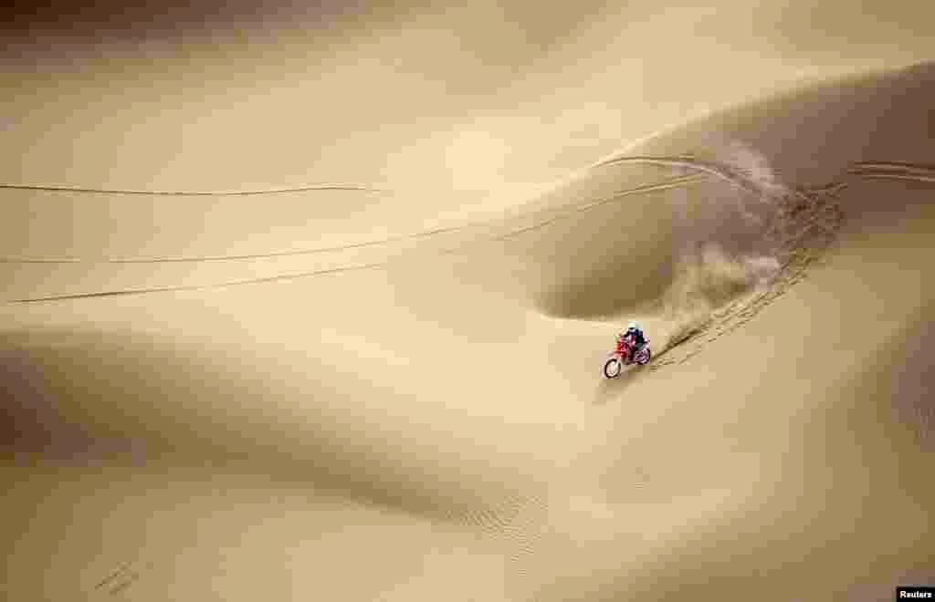 Wang Yirong of Hebei province rides his motorcycle in a desert during the China Taklimakan Rally and CCR Xinjiang Station, in Shanshan, Xinjiang Uighur Autonomous Region, May 31, 2014.