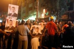 2013年7月30日,在埃及首都开罗东面的一个清真寺附近,被推翻的总统穆尔西的支持者和宗教学者参与反对军方的示威集会。
