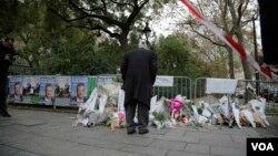 2015年11月14号在巴黎袭击事件后有人在看每天留在音乐厅外的纪念物。