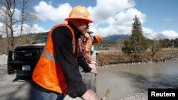 Nhân viên cứu hộ quan sát sông Stillaguamish gần khu vực nơi xảy ra vụ đất sạt lở gần Oso, Washington, ngày 23/4/2014.