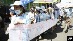 In this photo taken on Friday, May 4, 2012, Cambodian protesters from Boueng Kak lake march with a banner displaying the thumb prints of fellow land owners who have been evicted from their homes, as they demand compensation, in Phnom Penh, Cambodia. Cambo