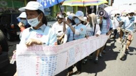 In this photo taken on Friday, May 4, 2012, Cambodian protesters from Boueng Kak lake march with a banner displaying the thumb prints of fellow land owners who have been evicted from their homes, as they demand compensation, in Phnom Penh, file photo.
