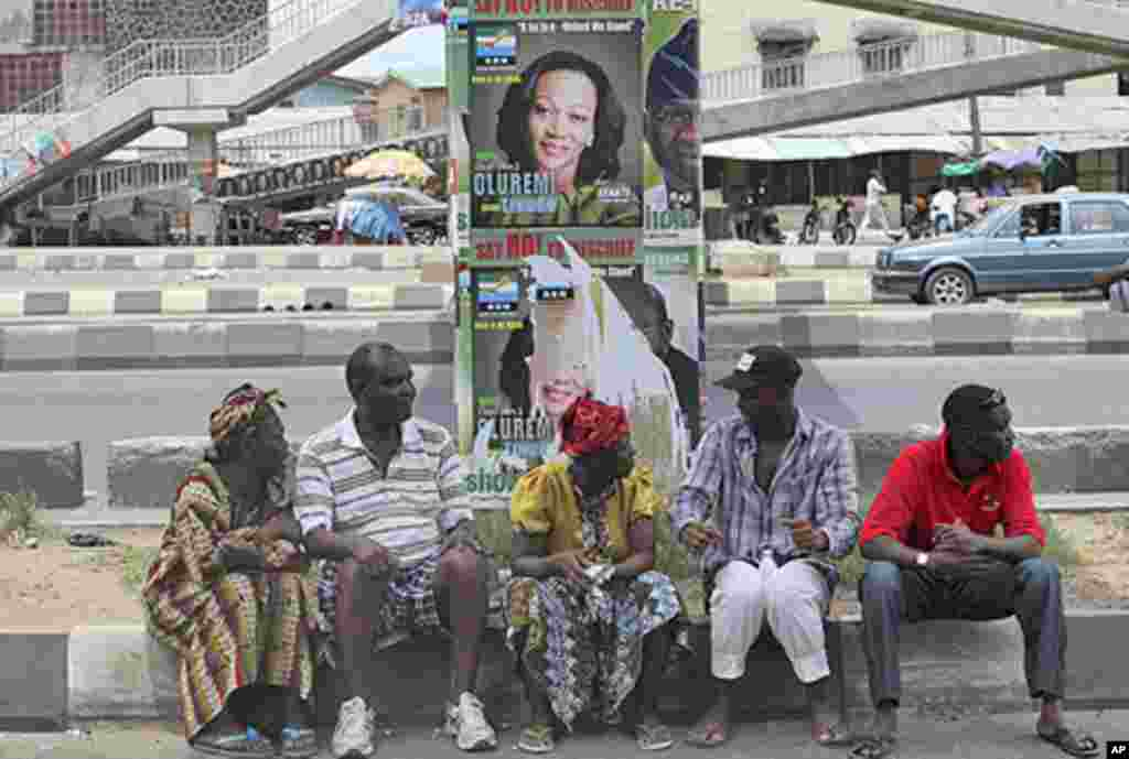 People sit under a bridge with election posters as they wait to cast their votes at a polling unit during the parliamentary election in the Ojuelegba district in Nigeria's commercial capital Lagos April 9, 2011. Nigerians voted in a delayed parliamentary