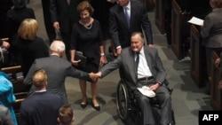 2018年4月21日,在美国德克萨斯州休斯顿的圣马丁主教教堂,前总统老布什参加芭芭拉·布什的葬礼后,前总统小布什推着坐在轮椅上的父亲离开会场。
