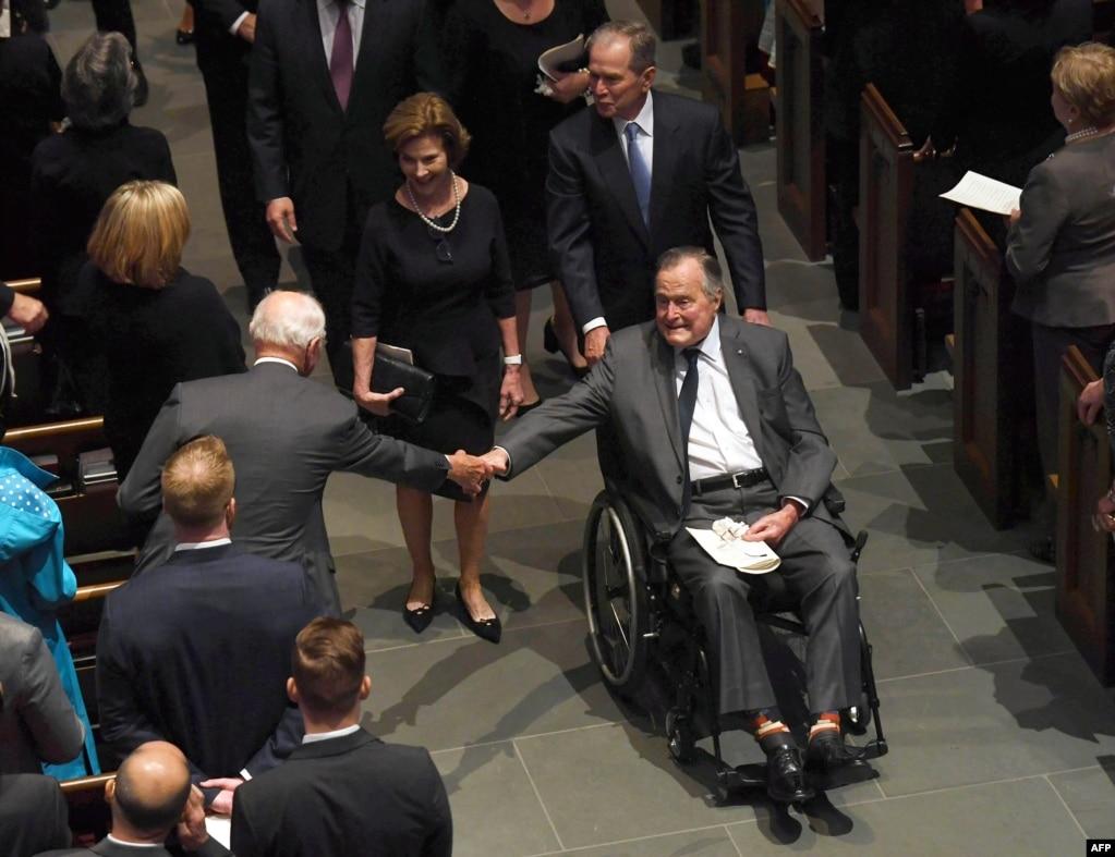 2018年4月21日,在美國德克薩斯州休斯頓的聖馬丁主教教堂,前總統老布什參加芭芭拉·布什的葬禮後,前總統小布什推著坐在輪椅上的父親離開會場。