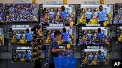 一名妇女和男孩走过北京商场的电视销售区。(2018年7月11日)