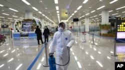 Petugas Korea Utara (mengenakan pakaian pelindung) menyemprotkan cairan desinfektan di Bandara Internasional Pyongyang , 1 Februari 2020. (Foto: dok).