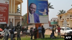 28일 중앙 아프리카 수도 방기 People stand under the poster of Central Africa Republic's President Francois Bozize in Bangui on December 28, 2012