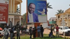 People stand under the poster of Central Africa Republic's President Francois Bozize in Bangui on December 28, 2012