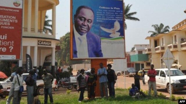 Residentes de Bangui ao pé de um poster do presidente da República Centro Africana, François Bozizé, 28 Dezembro 2012