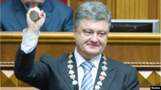 Ukraine's President Petro Poroshenko shows the presidential seal during his inauguration ceremony in the parliament hall in Kyiv, June 7, 2014.