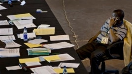 A tired election worker sits to make a phone call surrounded by his papers at the National Tallying Center.