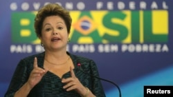 Brazil's President Dilma Rousseff gestures during an announcement of the construction of the first 50 port terminals for private use (TUP), at the Planalto Palace in Brasilia, July 3, 2013.