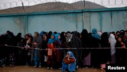 Afghan women stand in line to vote at a polling station in Kabul April 5, 2014.