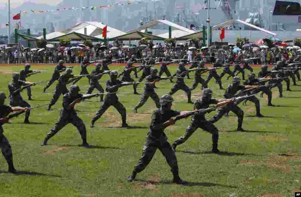 Personel Tentara Pembebasan Rakyat (PLA) People's Liberation Army (PLA) melakukan aksi dengan senjata dalam pembukaan Pangkalan Angkatan Laut Pulau Stonecutter di Hong Kong, yang menandai peringatan 18 tahun diserahkannya Hong Kong ke China (1/7). (AP/Kin Cheung)