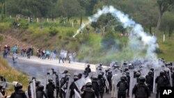 Policías antimotines lanzan gas lacrimógeno a estudiantes y manifestantes de la escuela de Ayotzinapa, para bloquearles el paso hacia Chilpancingo.