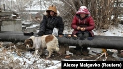 "Sasha, 49, nicknamed ""Poltorashka"" (a 1.5-liter beverage bottle) and Lyusya Stepanova, 44, both of whom are homeless, sit on a warm pipe with their dog, Bim, as they share a meal in Omsk on December 3, 2019."