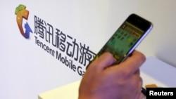 在北京舉行的全球移動互聯網會議上一名參觀者在騰訊展台前玩智能手機上的遊戲。 (2015年4月28日)