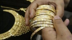 A buyer in Jammu, India chooses gold jewelry