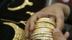 A buyer in Jammu, India chooses gold jewelry. Gold is commodity traded worldwide and in futures markets