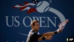 """Petenis Perancis Paul-Henri Mathieu, mengembalikan bola ke arah petenis Jerman Tommy Haas dalam putaran pertama kejuaraan tenis terbuka AS """"US Open"""" 2013, 27 Agustus, 2013, di New York. (AP Photo / David Goldman)."""