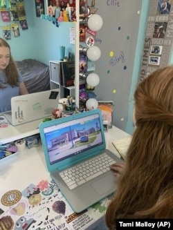 In this April 10, 2020 photo made available by Tami Malloy, Grace Malloy watches a virtual tour of the University of Colorado, while at home in Forest Grove, Oregon.