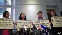 Mantan pembantu rumah tangga Indonesia di Hong Kong, Erwiana Sulistyaningsih (dua dari kiri) dan pendukungnya memegang plakat pada sebuah konferensi pers di Hong Kong, Jumat, 22 Desember 2017.