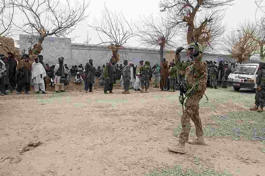 Un soldado estadounidense dirigiendo el tráfico cuando los ciudadanos afganos se congregan en Panjwai.