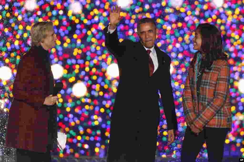 El presidente Obama saluda junto a su hija Malia y la actriz Jane Lynch, durante la ceremonia de iluminación del árbol navideño de la Casa Blanca.