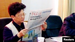 FILE - Yang Xiuzhu reads newspaper during meeting in Wenzhou, Zhejiang province, China, Dec. 29, 2001.