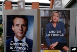 Election campaign posters for French centrist presidential candidate Emmanuel Macron and far-right candidate Marine Le Pen are posted in front of a polling station in Henin Beaumont, northern France, May 6, 2017.