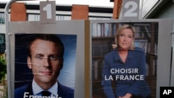 Poster kampanye pemilu capres berhaluan tengah, Emmanuel Macron, dan kandidat haluan kanan jauh, Marine Le Pen diperagakan di depan TPS dimana Marine Le Pen akan menggunakan hak suaranya di Henin Beaumont, sebelah utara Perancis, hari Sabtu, 6 Mei 2017 (foto: AP Photo/Francois Mori)