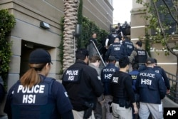 FILE - Federal agents enter an upscale apartment complex, Tuesday, March 3, 2015, in Irvine, Calif. Shortly after sunrise, federal agents swarmed the complex in the Orange County where authorities say a birth tourism business charged pregnant women $50,000