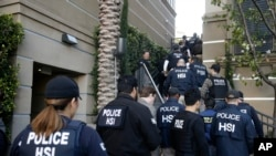 Federal agents enter an apartment complex March 3, 2015, in Irvine, Calif. to investigate a birth tourism business.